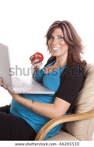 A pregnant business woman sitting and working on her lap top while eating fruit. - stock photo