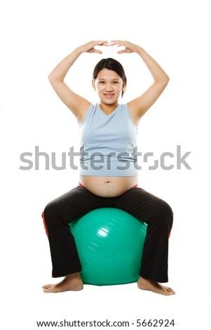 A pregnant woman exercising with an exercise ball - stock photo