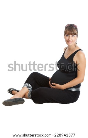 A pregnant woman, 9 months, sitting - stock photo