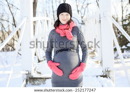 A pregnant woman's with belly in winter - stock photo