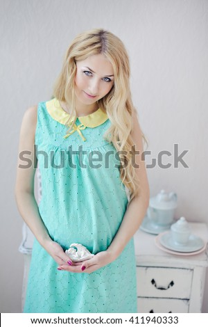 A pregnant woman with blond hair in mint color dress holds in her hands a clay figurine, a look at the camera. - stock photo
