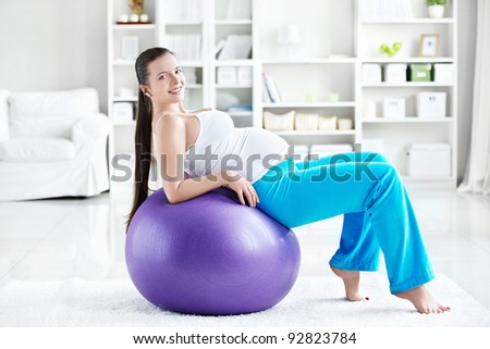 A pregnant young woman is doing on fitball - stock photo