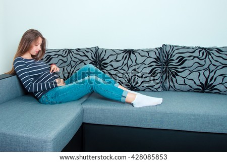 A pregnant young woman sitting on a couch , holding her stomach - stock photo