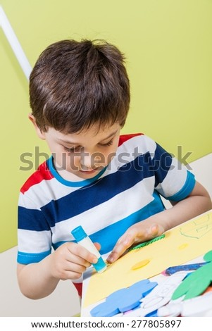 A preschool boy use glue for homework received from kindergarten - stock photo