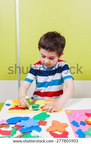A preschool boy use glue for homework received from kindergarten - stock photo