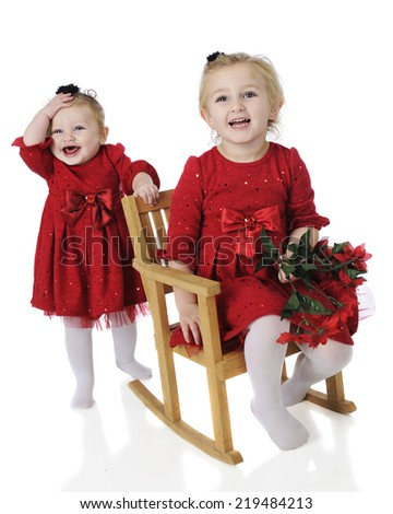 A preschooler and her baby sister all dressed up for Christmas.  Both are laughing in their identical red dresses.  On a white background. - stock photo