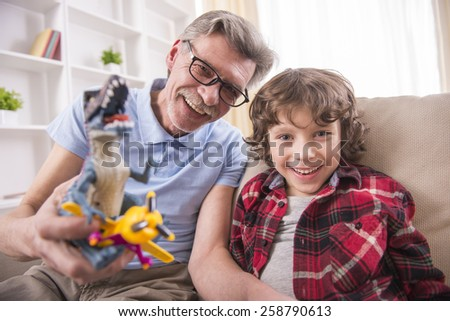 A preschooler and his grandpa happily are playing with toy dinosaurs. - stock photo