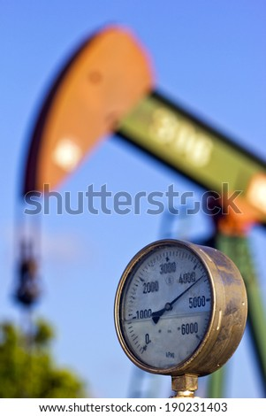 A pressure gauge and an oil pump at sunset - stock photo
