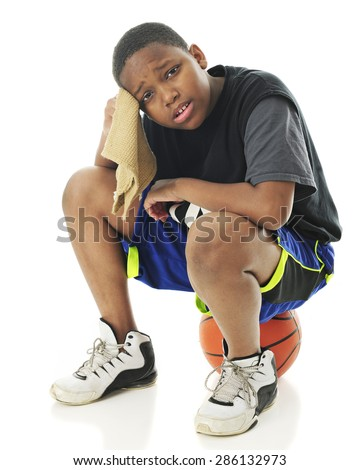 A preteen athlete looking distressed and wiping his brow as he sits on his basketball.  On a white background. - stock photo