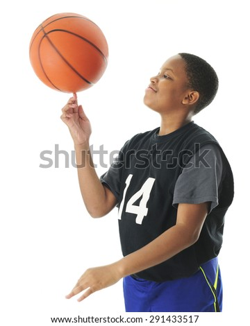 A preteen boy happily spinning his basketball on his index finger.  Motion blur on the ball,  On a white background. - stock photo