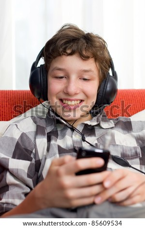 A preteen boy having fun as he listens to his mp3 player through big headphones on his head. He's seated on an orange couch with white pillows and he's wearing a checkered dress shirt. - stock photo