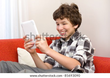 A preteen boy loves reading his electronic book while he sits on an orange sofa. - stock photo