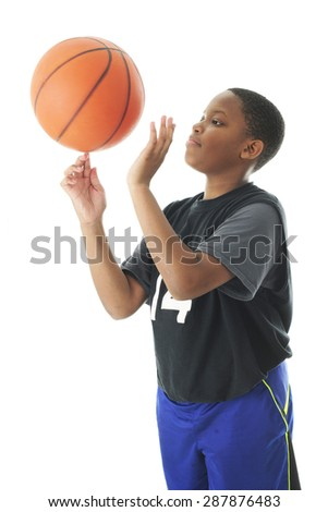 A preteen boy successfully spinning a basketball on an index finger.  Motion blur on the ball.   On a white background. - stock photo