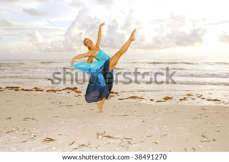 A pretty adult female ballerina is dancing on the beach with her leg kicked up high in a classic ballet pose with seagull in background. - stock photo