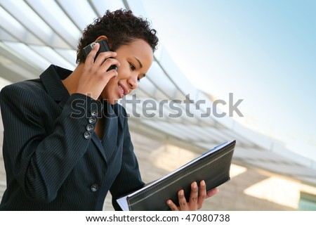 A pretty african american business woman at her company on the phone - stock photo