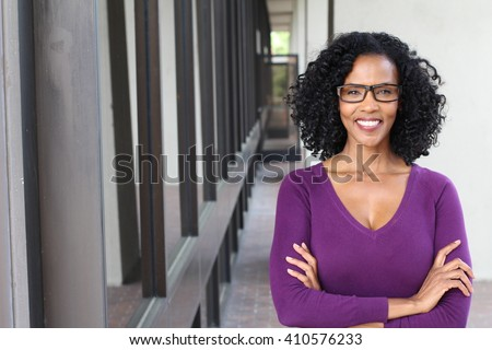 A pretty African american woman wearing glasses at work - stock photo