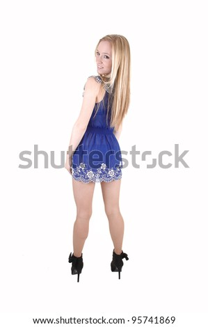 A pretty and slim young woman standing in her blue short dress and  long blond hair and black boots for white background in the studio. - stock photo