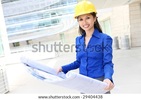 A pretty asian woman working as architect on a construction site - stock photo