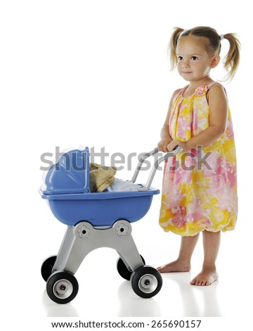 "A pretty, barefoot preschooler pushing her rag doll ""baby"" in a doll buggy.  On a white background. - stock photo"