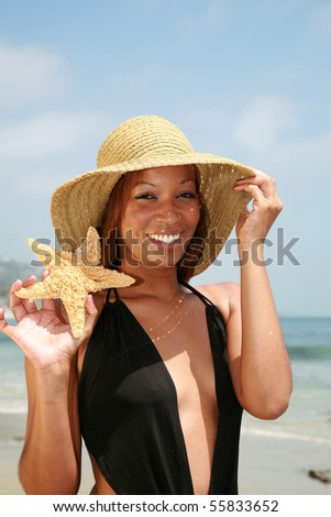 a pretty black chick in a sun hat holds a starfish at the beach - stock photo
