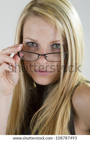 A pretty blond girl looking intently into the camera over her eyeglasses. - stock photo