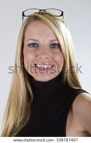 A pretty blond girl with her eyeglasses on top of her head smiles big for the camera. - stock photo