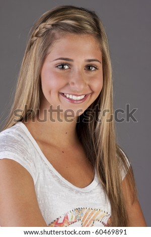 a pretty blond young teen girl standing with folded arms. - stock photo