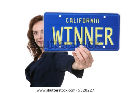 A pretty business woman holding a winner license plate - stock photo