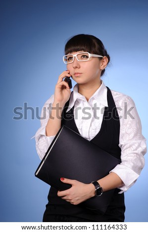 A pretty business woman sitting at table and calling - stock photo