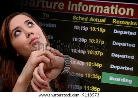 A pretty business woman traveling looking at departure times - stock photo