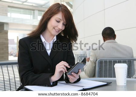 A pretty business woman working outside at a table - stock photo
