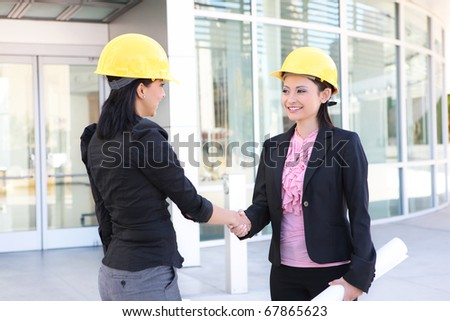 A pretty business women handshake doing construction at office building - stock photo