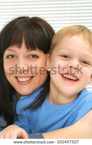 A pretty Caucasian mother and son a light background - stock photo