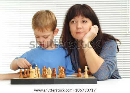 A pretty Caucasian mother and son playing chess against a light background - stock photo