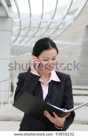 A pretty Chinese business woman smiling outside office building on phone - stock photo