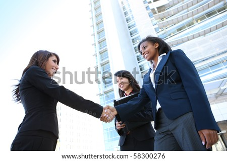 A pretty diverse young business woman team at office building handshake - stock photo