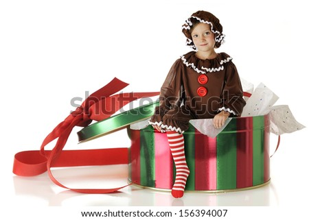 A pretty elementary gingerbread girl climbing out of a red and green cookie tin.  On a white background. - stock photo