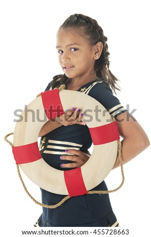 A pretty elementary girl in a sailor dress.  She's looking the the viewer while holding a life ring.  On a white background. - stock photo