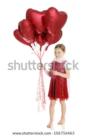 A pretty elementary girl in red and loaded up with a white boa, strands of hearts and a big bouquet of red, heart-shaped balloons.  On a white background. - stock photo