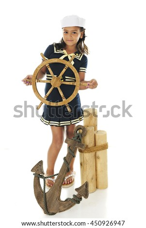 """A pretty elementary """"sailor  girl"""" looking at the viewer as she stands by mooring posts, an anchor and holding a ship's wheel.  On a white background. - stock photo"""
