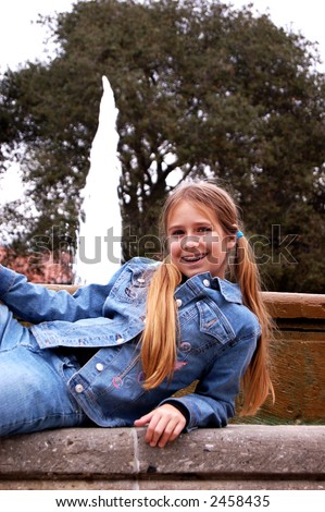 A pretty eleven year old girl lying in front of a fountain. - stock photo