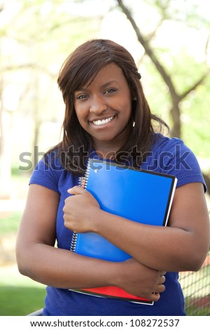 A pretty female African-American college or university student holding books, outdoors - stock photo