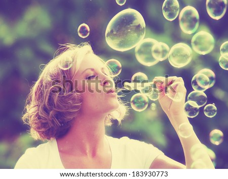 a pretty girl blowing bubbles - vintage toned with a retro instagram filter - stock photo