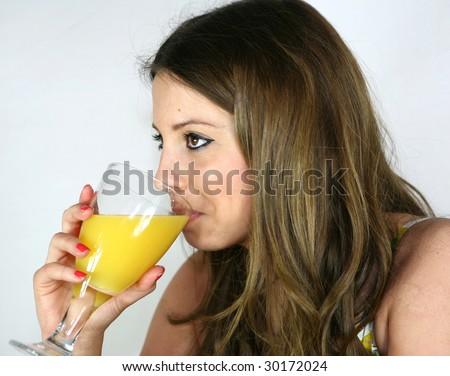 A pretty girl drinks a glass of orange juice - stock photo