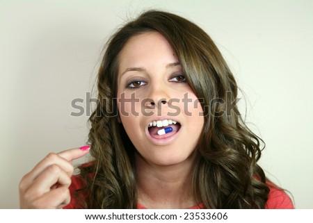 A pretty girl takes a pill. - stock photo