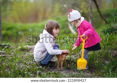 A pretty happy little girl in a pink jacket and white hat  and a young boy playing with a tiny dog in cool weather in a forest. Kids and nature. - stock photo