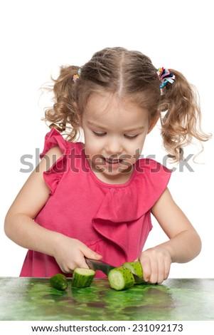 A pretty little girl cuts a cucumber - stock photo