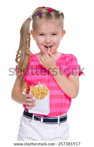 A pretty little girl eats fries on the white background - stock photo