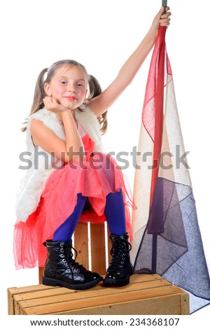 a pretty little girl sitting on a box with a french flag on the white background - stock photo