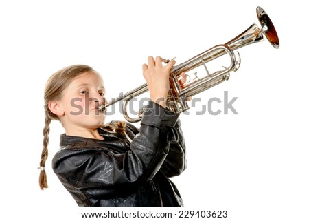 a pretty little girl with a black jacket plays the trumpet on the white background - stock photo